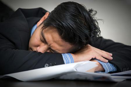 Tired overworked businessman sleeps on desk photo