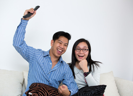 blacking: Young Asian couple watching television at home in living room