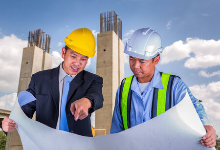 Asian engineer and worker leader discus for drawing detail in construction site photo