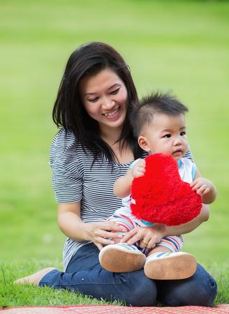 Schöne Asien Mutter und Baby im Freien. Natur. Schönheit Mama und ihr Kind beim Spielen im Park zusammen. Outdoor Portrait der glücklichen Familie. Freude. Mama und Baby Standard-Bild - 30725759