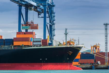 Container Cargo Frachtschiff mit Kran arbeiten in der Werft Ladebrücke in der Abenddämmerung für Logistic Import Export Hintergrund Standard-Bild