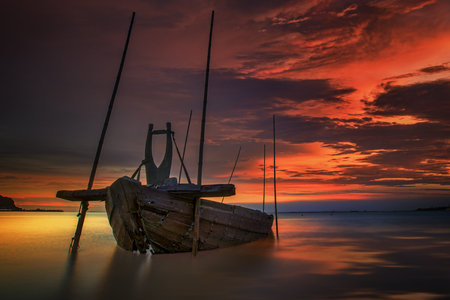 ship wreck: Fishing boat beached with sunset view Stock Photo