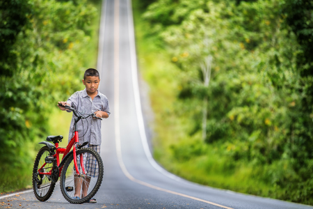 Asian boy riding on his bycicle in hard and hight road way photo