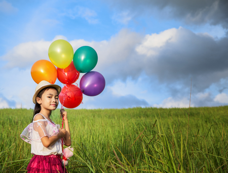 tightly: young asia girl holds tightly to a large bunch of helium filled balloons in nature park