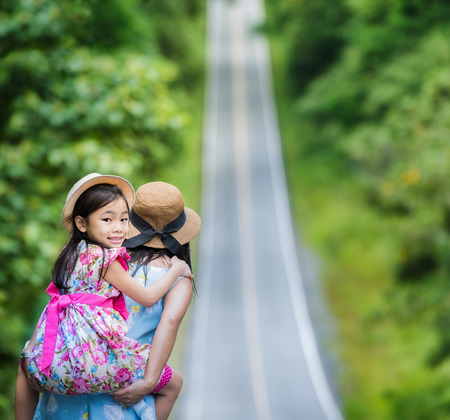 piggyback ride: Small happy girl enjoying a piggyback ride on his mothers back and walk on the road. Stock Photo