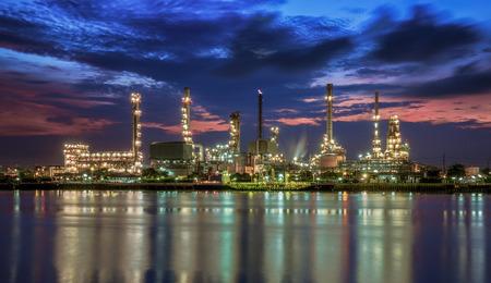 川の上の反射と夜の時間での石油化学プラント