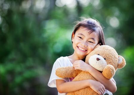 korean girl: Asia little girl with doll bear in nature park