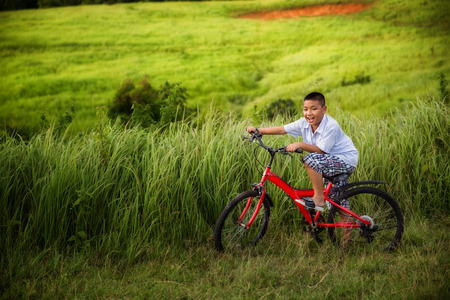 Asian boy riding on his bycicle in summer garden  photo