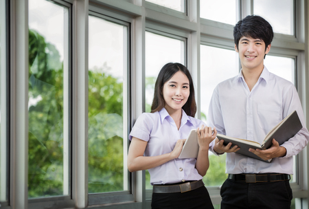collegian: Asia students read a book and use smart phone in Library with uniform Stock Photo