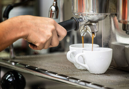 coffee house: prepares espresso in his coffee shop with hand and close up Stock Photo
