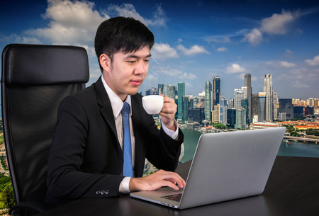Portrait of goodlooking Asian man sitting at table at working office with laptop computer, smiling at camera. and Singapore city backgroung photo