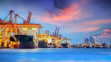 Containerladung Frachtschiff mit Arbeiten Kranbrücke in der Werft in der Abenddämmerung für Logistic Import Export Hintergrund Standard-Bild - 31721432