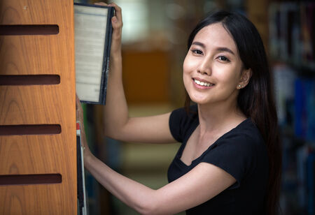 thai student: A portrait of a mixed race college asia student at campus in library