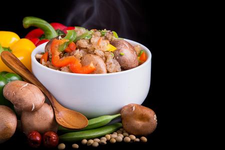 frijoles rojos: arroz frito vegetariano con el material vegetal en la placa arbolada en fondo negro aislado.