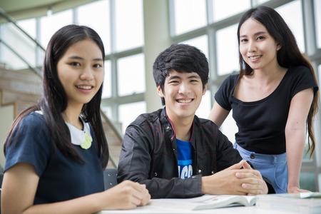 アジアの学生グループは図書館で本を読む