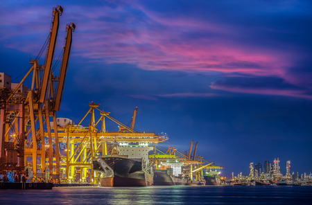 export import: Container Cargo freight ship with working crane bridge in shipyard at dusk for Logistic Import Export background