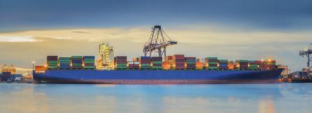 コンテナー貨物船ロジスティック インポートエクスポートの背景の夕暮れ時に造船所の橋を読み込みクレーンを使っています。