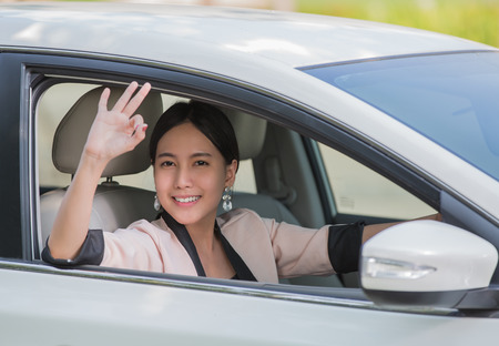 Glimlachende gelukkige jonge vrouw in de auto en zegt OK