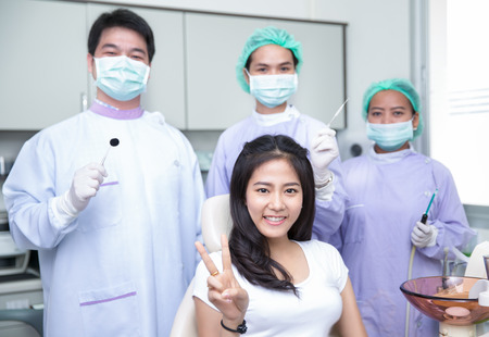 Beautiful asian woman sitting at the dentist while smiling towards the camera