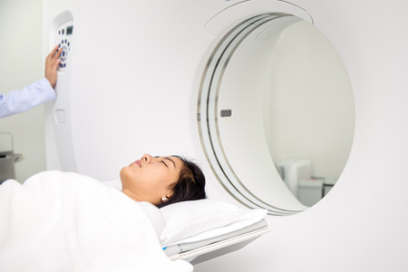 Asian lady sleep on a CT Scan bed and panel control by Radiologic technician photo