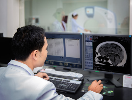 Medical team operating computers in CT scan lab for head section