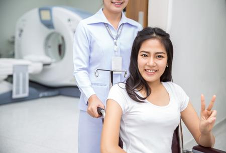 examenes de laboratorio: Se�ora asi�tica que se sienta en wheelshair despu�s del examen de su cuerpo por una tomograf�a computarizada con la enfermera Foto de archivo
