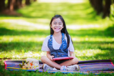 Funny little Asian girl learning with tablet pc in the park photo