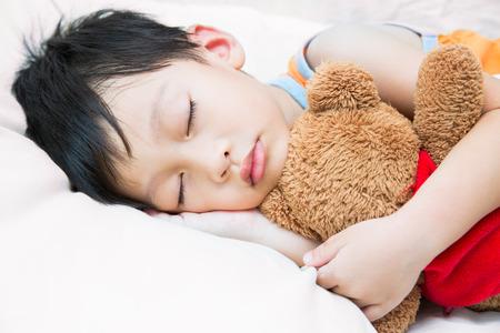 dormir: Asia niño que duerme con el oso de peluche Foto de archivo