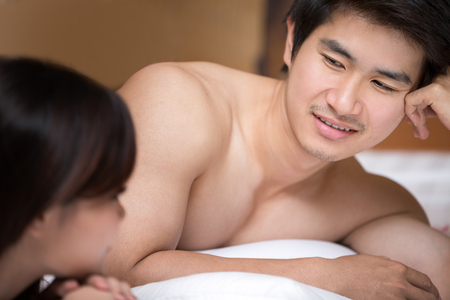 A happy young couple lying on the bed in a asian style hotel room.