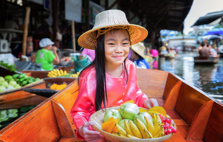 seller: Chikd sit on the boat and hold the fruit basket in Traditional floating market , Thailand. Stock Photo