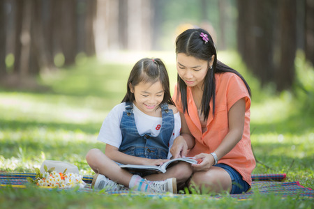 Mon and baby take a home work on the green nature and flower garden. photo