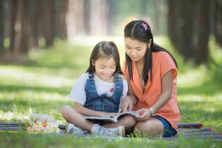 madre trabajando: Mon y el beb� tienen un trabajo a domicilio de la naturaleza y de la flor verde jard�n.