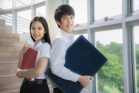 Azië leerlingen lezen een boek in de bibliotheek met een uniforme
