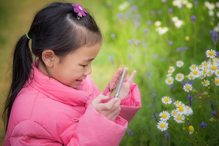 niños sonriendo: Bebé tomar una fotografía de la naturaleza por el teléfono inteligente
