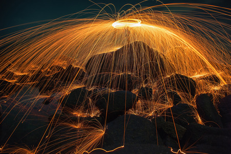 rock wool: Showers of hot glowing sparks from spinning steel wool on the rock and beach