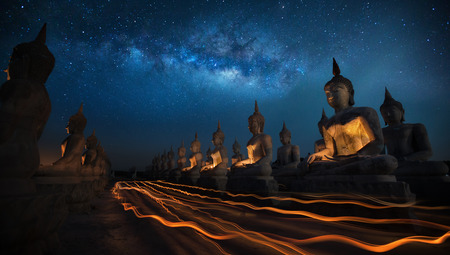 Thai people in Candly festival with Buddha statue and milky way in dark night sky in Thailand Imagens - 38178466