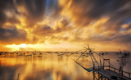 fish net: Fisherman tool with sunrise,with orange sky ,at Pakpra, Phatthalung ,Thailand Stock Photo