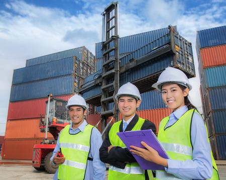 Team van jonge logistieke mensen uit het bedrijfsleven bijeen in logistieke poort. Stockfoto