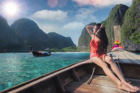 picknic: Asian lady relax on long tail boat at maya beach, Phi Phi island near Phuket in Thailand Stock Photo