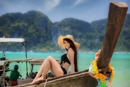 Asian lady take holiday in wooded boat in Maya beach, Phi Phi, Thailand Stock Photo