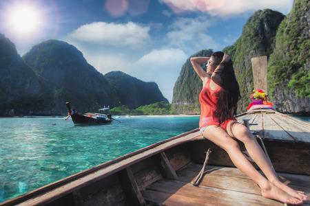 아시아 여성은 마야 비치, 태국 푸켓 근처 피 피 섬에서 긴 꼬리 보트에서 휴식 스톡 콘텐츠