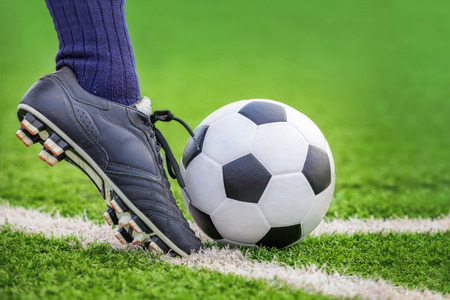 pies masculinos: Dispara a un balón de fútbol con los pies en el campo de fútbol Foto de archivo