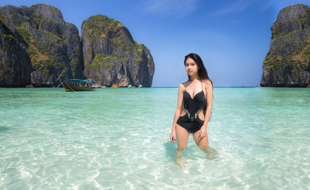 picknic: Asian lady relax with long tail boat at maya beach, Phi Phi island near Phuket in Thailand Stock Photo