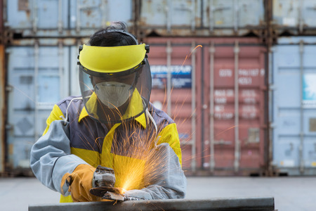 Worker take hard work with Electric wheel grinding on steel structure in factory Stock Photo