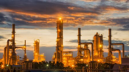 Oil refinery factory with sunrise background, Pipe, oil tank and factory, energy and air polution concept. Stock Photo