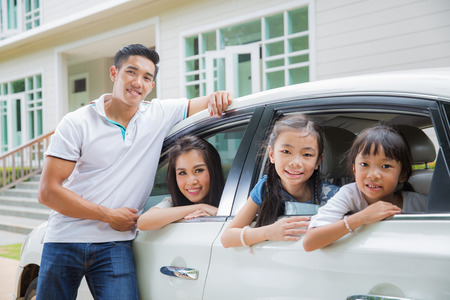 Beautiful family portrait smiling outside their new house, just arrive new home by car. Stok Fotoğraf