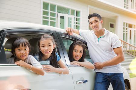 車で新しい家に到着ちょうど美しい家族の肖像画は彼らの新しい家の外笑顔します。 写真素材