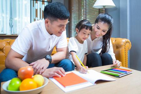 Vader en Mather leren en ontspannen met hun dochter om thuiswerk te doen door te tekenen en schilderen, familie, kinderen, onderwijsconcept.
