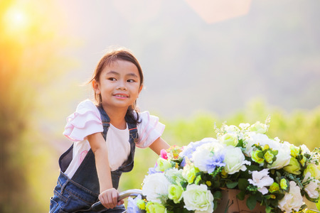 Portrait of a beautiful Asian girl holding bouquet of flowers in the park while riding a vintage bycicle, Thai, asia children concept.