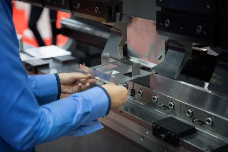 Operateur buigmetaalplaat door bladbuigmachine, productiewerkproces in gefabriceerde fabriek door werknemer, handmatige of semi-automatische verwerking. Stockfoto